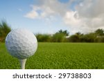 golf ball and tee on lush tropical course with copy space - stock photo