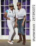 Small photo of Bisbee, Arizona, USA, April 6, 2015, Phylis Tampio and Leslie Plimpton pose in front of purple draped doorway