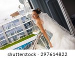 Small photo of Attractive bride is standing on the balcony, looking jilt and smile.