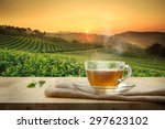 Stock photo cup of hot tea with sacking on the wooden table and the tea plantations background 297623102