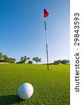golf ball on green at ground level extreme wide angle (focus on ball) - stock photo