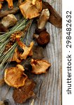 Small photo of Heap of Dried Forest Chanterelles, Porcini and Boletus Mushrooms with Dry Grass, Leafs and Fir Stems closeup in Rustic Wooden background