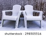 Two Snow Covered Lawn Chairs.