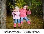 two sisters swinging outdoors... | Shutterstock . vector #298601966