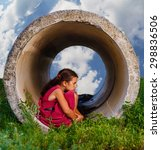 Small photo of Homeless teenager girl sits on his haunches in the concrete pipe ring ill agoraphobia sad picture on the street psychology