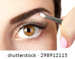 Young Woman Plucking Eyebrows...