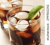 Small photo of Cocktail with cola and ice on wooden table. in a glass with a cocktail, put a slice of lime