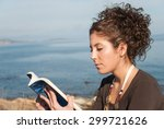 lady reading a book near the sea | Shutterstock . vector #299721626