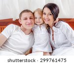 happy family lying on a bed... | Shutterstock . vector #299761475