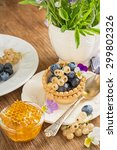 Small photo of Light fresh crunchy pastry tartlet of fresh blueberries and white currants on a la carte dishes with honey comb in the background Bunch of viola on a wooden background. selective Focus