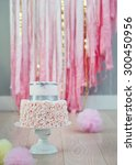 Small photo of Elegant two-tier birthday or wedding cake with ruffled fondant bottom, decorated with grey satin ribbon. Pastel pompoms on the wooden floor, fabric streamers in the background.