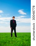serious businessman standing at the green grass - stock photo