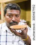 Small photo of MUMBAI, INDIA - 05 FEBRUARY 2015: Portrait of Indian man drinking milk tea in traditional style. Drinking hot tea from saucer makes it possible for tea to cool down quicker.