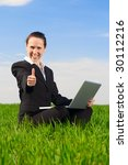 smiley woman with laptop showing thumbs up - stock photo
