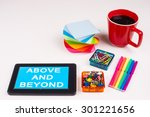Small photo of Business Term / Business Phrase on Tablet PC - Colorful Rainbow Colors, Cup, Notepad, Pens, Paper Clips, White surface - White Word(s) on a cyan background - Above And Beyond
