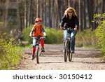 Mother and daughter riding on bicycles in the forest - stock photo