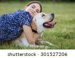Stock photo portrait of a woman with her beautiful dog lying outdoors training the dog 301527206