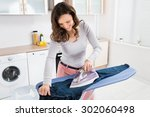 happy woman ironing trousers... | Shutterstock . vector #302060498