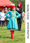 "Small photo of DAKHOVSKY, RUSSIA - JULY 25 2015: The girl Muslim in beautiful national Adyghe dresses dances traditional dance. The Festival ""Lago-Naki: Kunatskaya"" was held in the mountains of Adygea in Dakhovsky"