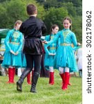 "Small photo of DAKHOVSKY, RUSSIA - JULY 25 2015: Children Muslims in beautiful national Adyghe suits dance traditional dance. The Festival ""Lago-Naki: Kunatskaya"" was held in the mountains of Adygea in Dakhovsky"