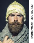 Small photo of Portrait of unsocial unshaven hobo man with long beard and hendlebar moustache in knitted yellow hat and grey scarf looking forward standing on black background, vertical picture
