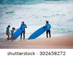 Small photo of BONDI BEACH, SYDNEY, AUSTRALIA - DECEMBER 12, 2014: Two male wave surfing instructors holding their blue surf boards looking after two happy girls, perhaps their students or daughters, at Bondi Beach