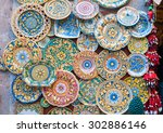Small photo of Various decorated pottery dishes hung for sale outside a souvenir shop in Erice, Sicily