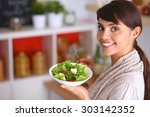 young woman eating fresh salad... | Shutterstock . vector #303142352