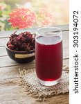 Small photo of Roselle juice on table, flower background, raw roselle in cup