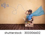 Small photo of Happy child playing in cardboard box. Kid having fun at home