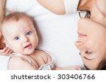 happy baby girl lying near her... | Shutterstock . vector #303406766