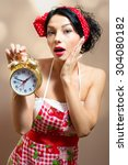 Small photo of Young pinup lady in Alice band, apron holding alarm clock