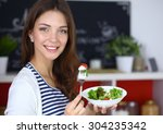 Young Woman Eating Salad And...