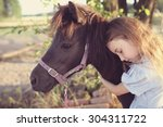 young girl hugs a pony on a farm | Shutterstock . vector #304311722