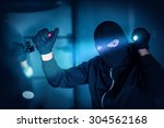 Car Thief Car Robbery Concept Photo. Caucasian Male Thief in Black Mask Trying to Open Car Using Custom Tool and Flashlight. Car Robber. - stock photo