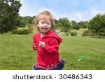 Toddler happily running through park - stock photo