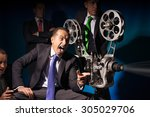Small photo of One and the same person looks at a vintage comedy movie projector