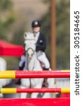 Equestrian Horse Rider Gate Equestrian horse rider blurred show jumping gates poles colors on arena course.