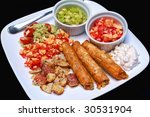 Mexican meat rolls and a healthy meal - stock photo