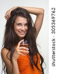 Small photo of Lovely brunette is holding flacon of parfume on the white background. Happy quean in orange shirt is laughing.