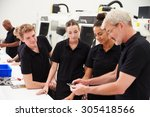 Small photo of Engineer In Factory With Apprentices Checking Components