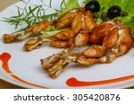fried frog legs with herbs on... | Shutterstock . vector #305420876
