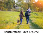 Stock photo happy family with dog walking in the meadow little girl sitting on dad s shoulder 305476892