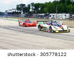 Elkhart Lake, Wisconsin USA - August 9, 2015: Road America road course, IMSA. Action Express Racing, Coyote Corvette DP, Mustang Sampling powered by Chevrolet leads the eventual race winner, pit lane. - stock photo