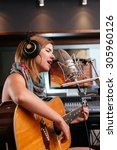 Small photo of Pretty Latin woman singing and playing guitar in recording studio