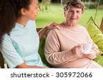 caring nurse and elder woman in ... | Shutterstock . vector #305972066