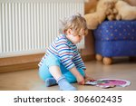 Stock photo little cute blond boy playing with puzzle game at home kid having fun indoors child development 306602435