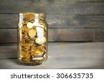 glass jar with coins on wooden... | Shutterstock . vector #306635735