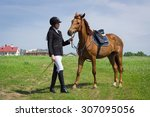 Small photo of Beautiful young girl jockey talks with her horse dressing uniform competition