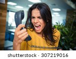 Small photo of Angry businesswoman shouting on phone in office